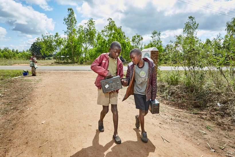 From left to right: Jan Chumba (12) and his brother Ben (10) carry two solar batteries home, after picking them up at Green M