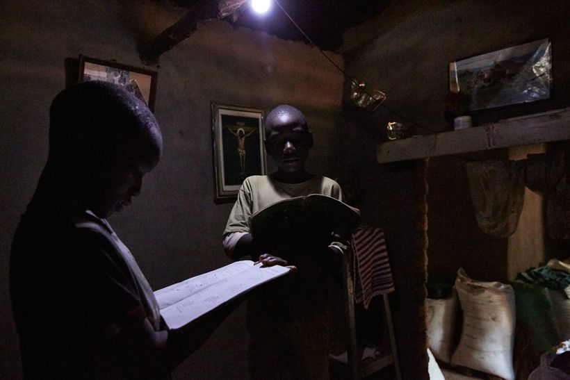 Jan Chumba (12) and his brother Ben (10) study using the light from a solar battery powered light bulb, Chiuta village, south