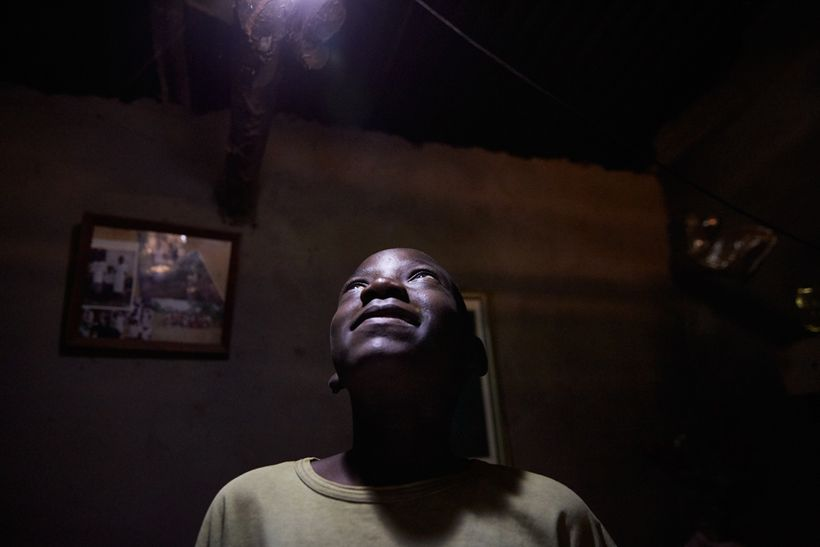 Jan Chumba (12) looks up at one of the light bulbs, Chiuta village, southern Malawi, 2017. Powered by a solar battery, the bu