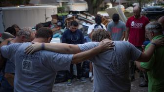 Samaritans  pray after helping clear furniture from the flooded house of a neighbor in the aftermath of Tropical Storm Harvey in Houston, Texas, U.S. September 3, 2017. REUTERS/Adrees Latif