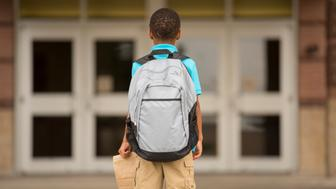 Back to school... Cute, African descent little boy ready for school. Lunch sack and backpack. School building background.