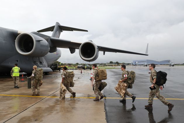 Soldiers board a Royal Air Force C-17 Globemaster III aircraft at Brize Norton, Oxfordshire, before they...