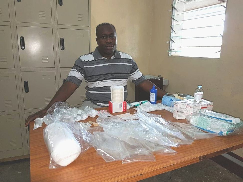 Dr. Wilfrid Mutombo sits with all the items needed to treat a single sleeping sickness patient.