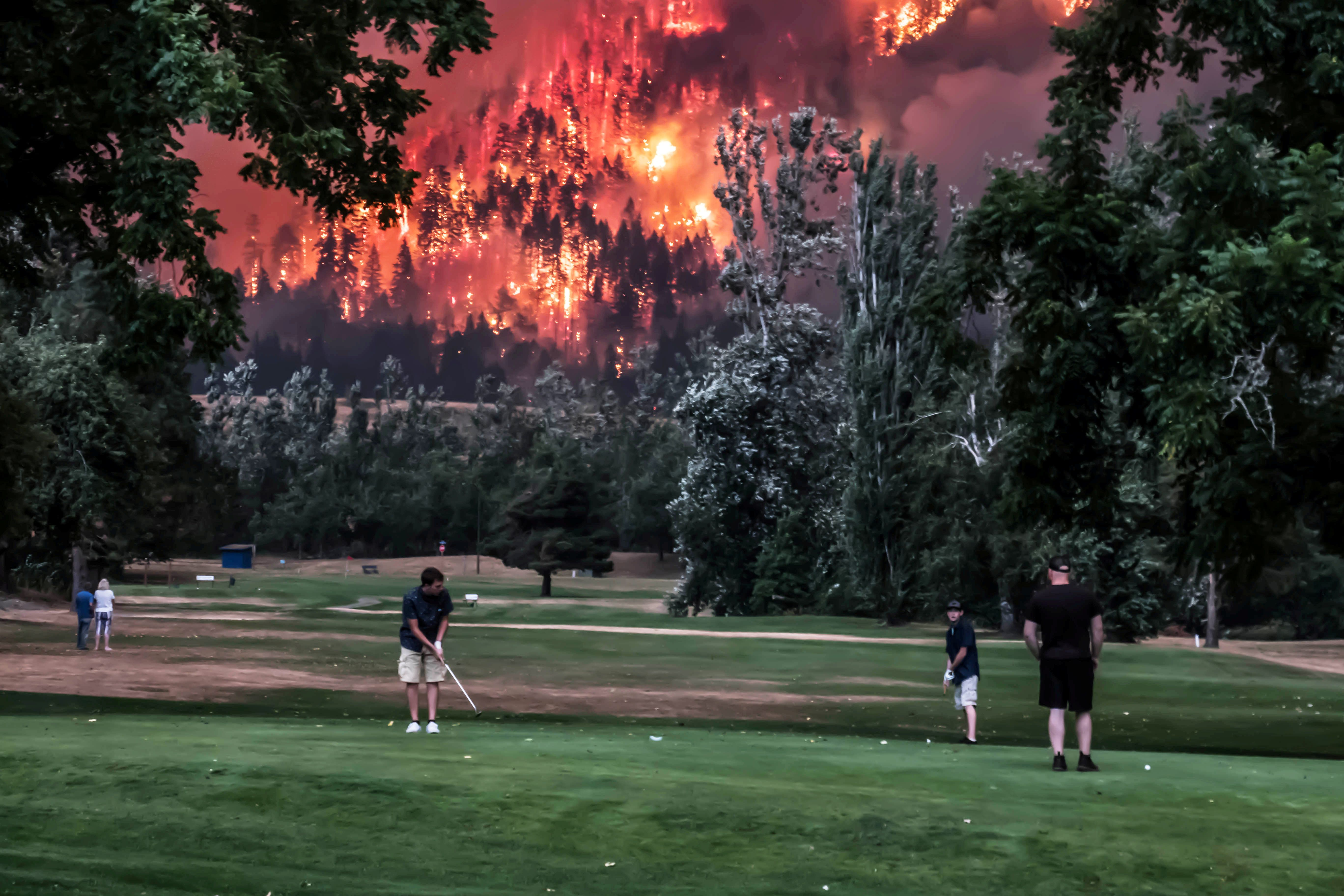 The Eagle Creek wildfire burns as golfers play at the Beacon Rock Golf Course in North Bonneville, Washington, on September 4
