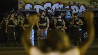 St Louis County police officers watch as anti-police demonstrators march in protest in Ferguson, Missouri August 10, 2015. Police in riot gear clashed with protesters who had gathered in the streets of Ferguson early on Tuesday to mark the anniversary of the police shooting of an unarmed black teen whose death sparked a national outcry over race relations. REUTERS/Lucas Jackson