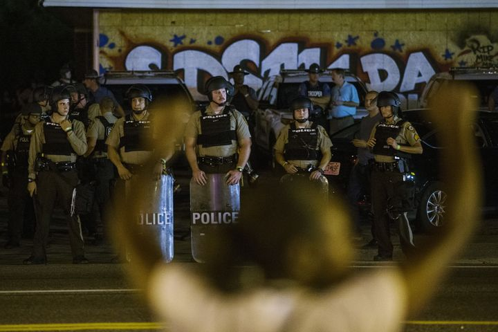 St Louis County police officers watch as anti-police demonstrators march in protest in Ferguson, Missouri August 10, 2015.