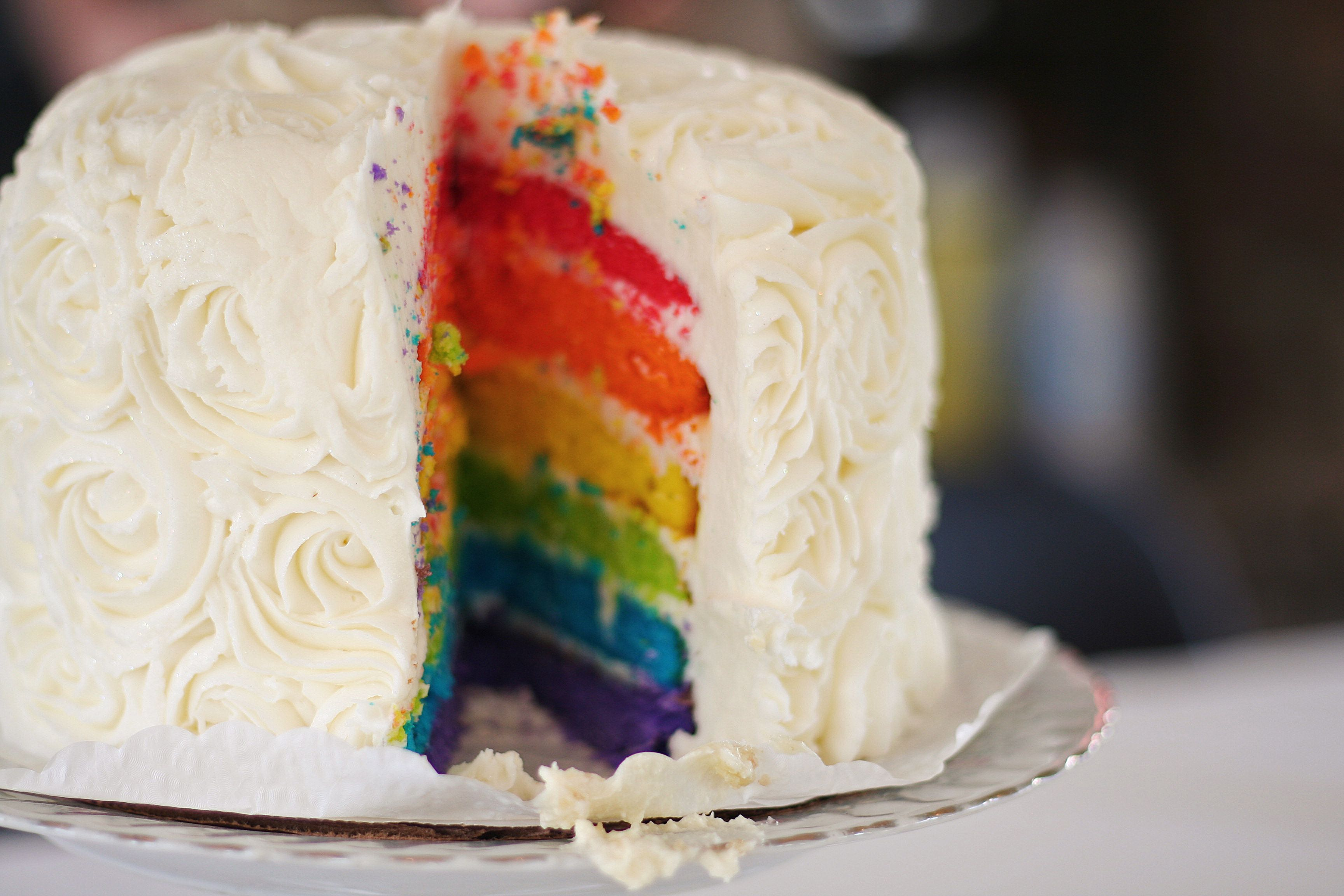 A white cake with rainbow layers.