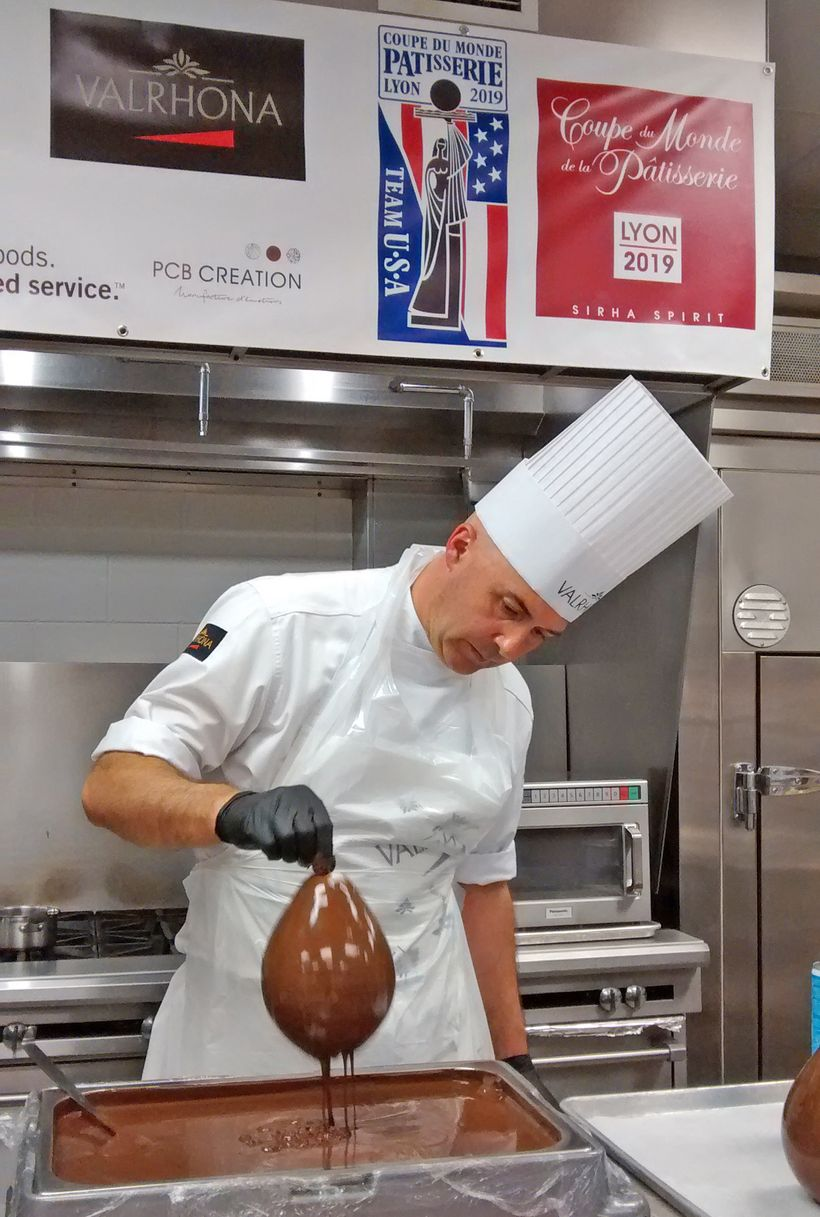 Olivier Saintemarie dips balloons in tempered chocolate to create the hourglass for his chocolate showpiece