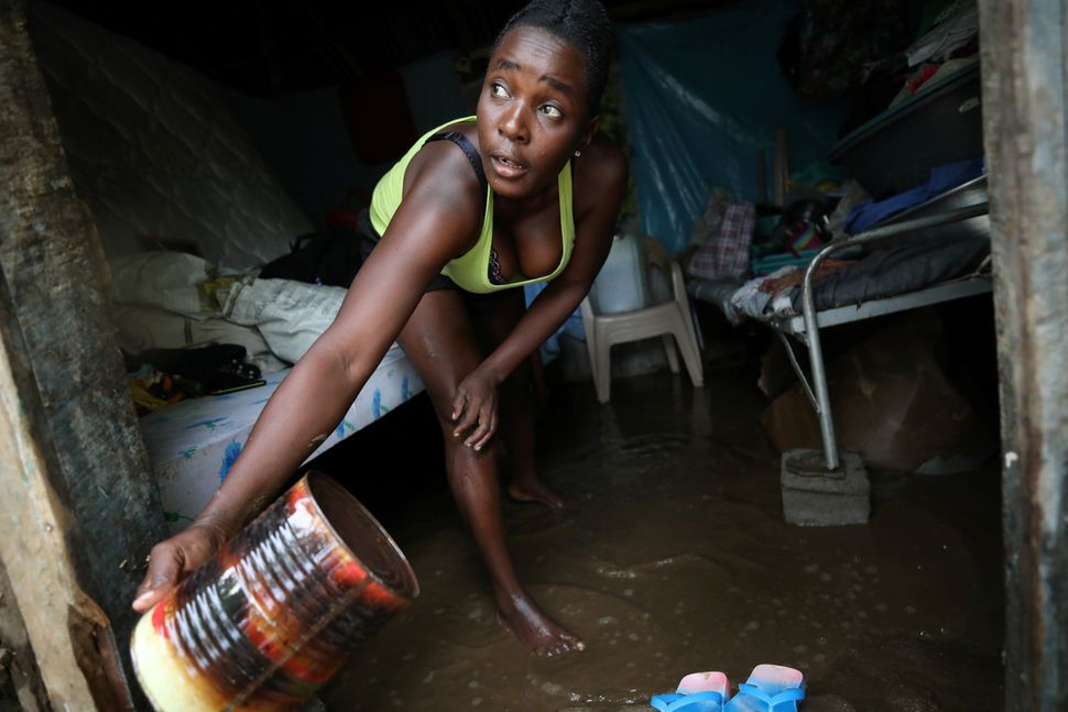 A woman uses a can to take water out of her house in a flooded area after hurricane Irma in Fort Liberte, Haiti