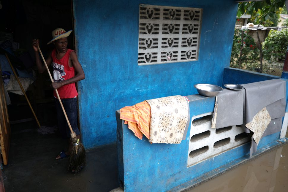 A man wipes water in his house in Fort Liberte, Haiti