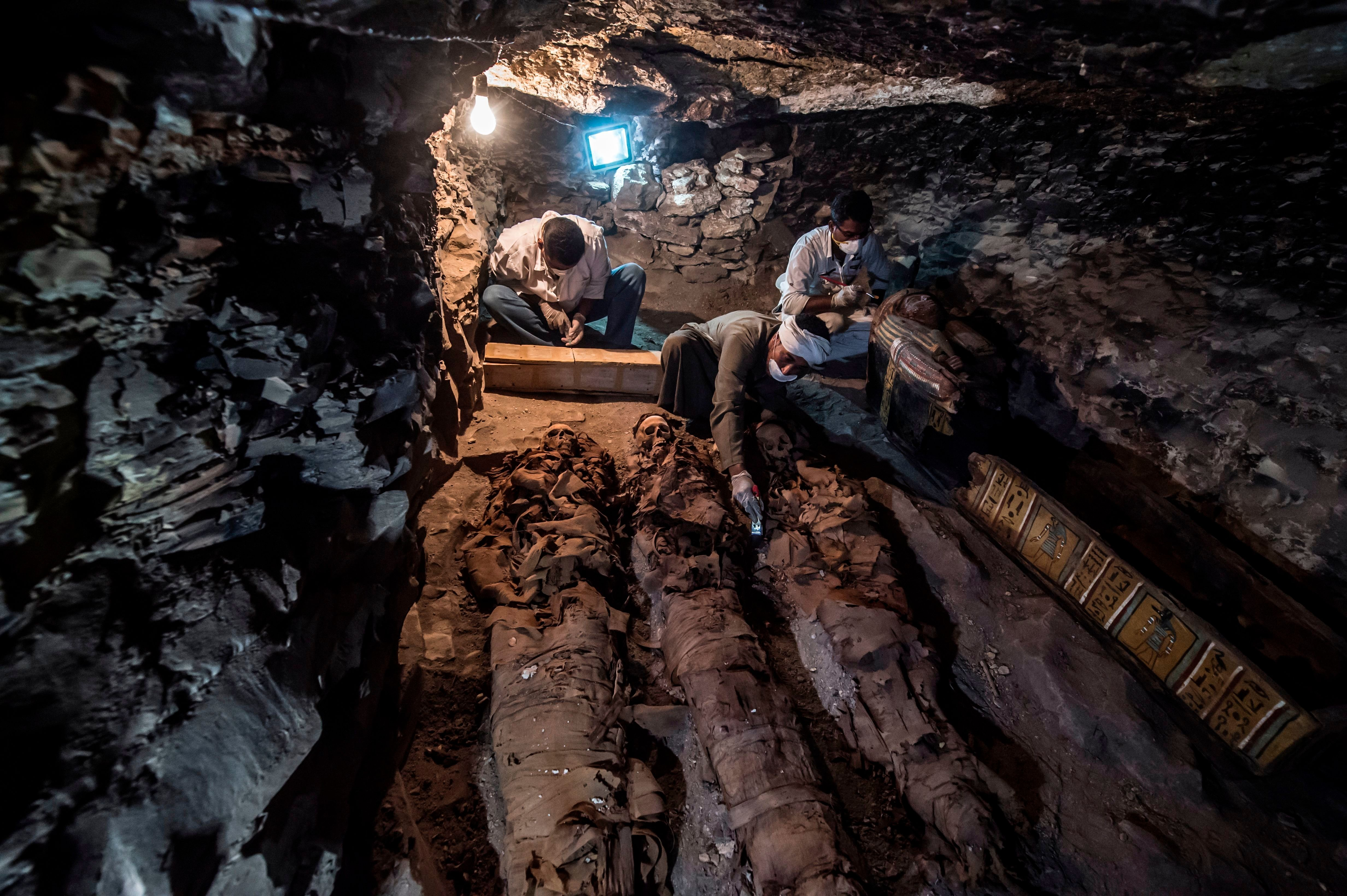 A picture taken on September 9, 2017 shows Egyptian labourers and archaeologists unearthing mummies at a newly-uncovered anci
