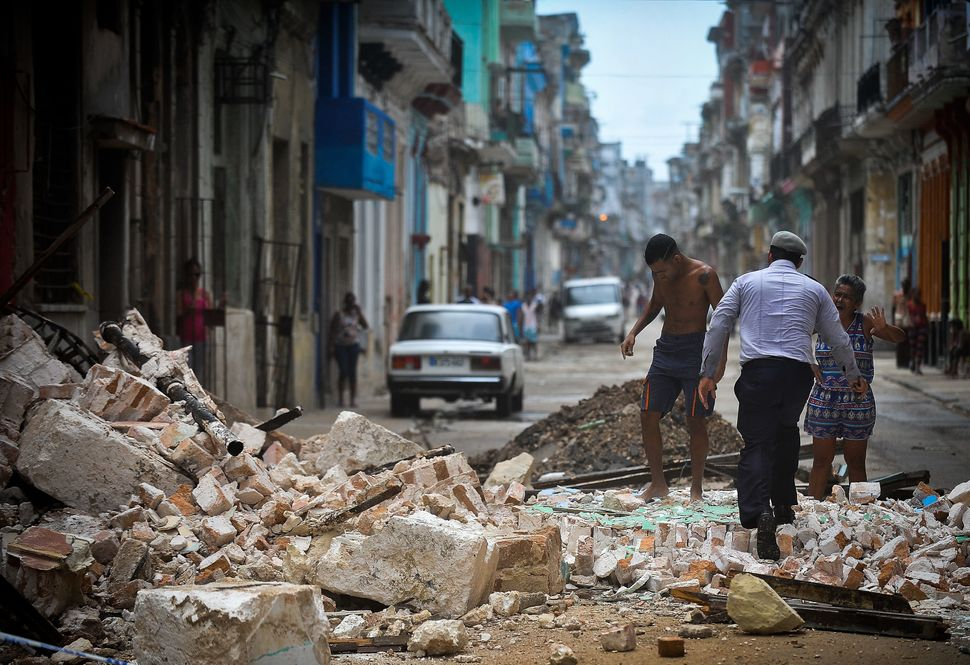 Cubans wade through rubble in Havana.