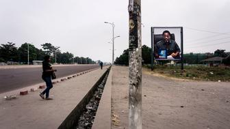 A Congolese women crosses an empty boulevard in Kinshasa with a placard of President of the Democratic Republic of Congo Joseph Kabila as the opposition leaders called for two days of general strikes on July 8, 2017 in Kinshasa. Opposition supporters are demanding the publication of an electoral calendar, elections and Kabila's departure from office. / AFP PHOTO / JOHN WESSELS        (Photo credit should read JOHN WESSELS/AFP/Getty Images)
