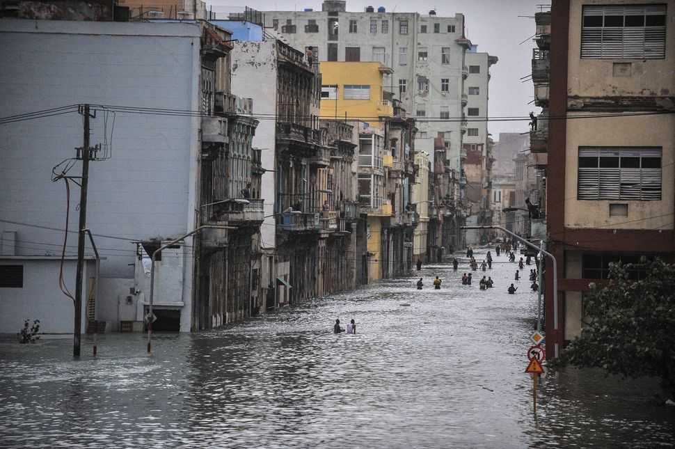 Cubans wade through a flooded street in Havana.