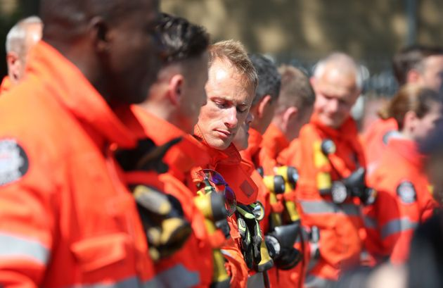 Members of the emergency services gather to observe a minute's silence near to Grenfell