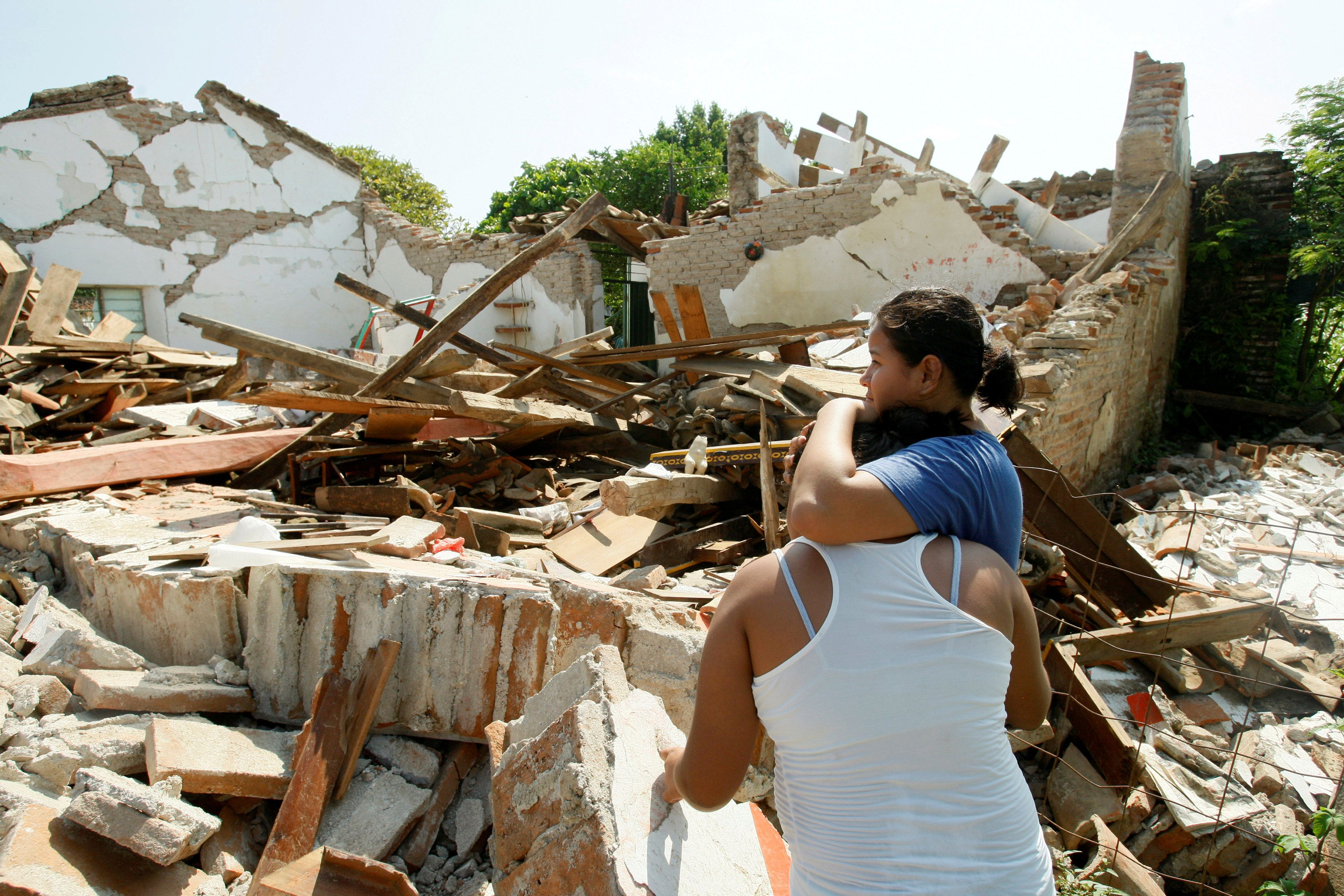 Women hug while standing next to a destroyed house after an earthquake struck the southern coast of Mexico late on Thursday, in Union Hidalgo, Mexico September 9, 2017. REUTERS/Jorge Luis Plata     TPX IMAGES OF THE DAY