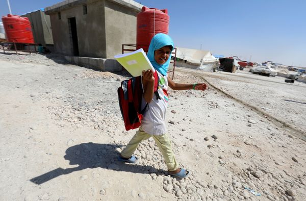 A displaced child from the Islamic State group's Syrian stronghold of Raqa walks to attend the first day of the new school ye