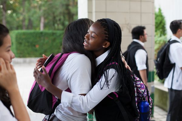 Caroline Mogomela hugs Yesenia Villada on her first day of school at St. Patrick Secondary School in Toronto.