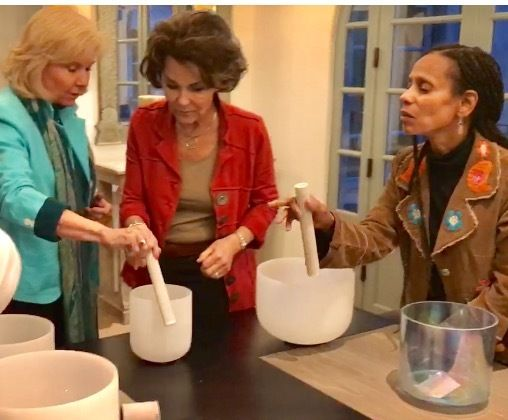 Flicka teaching crystal singing bowls during sound healing workshop