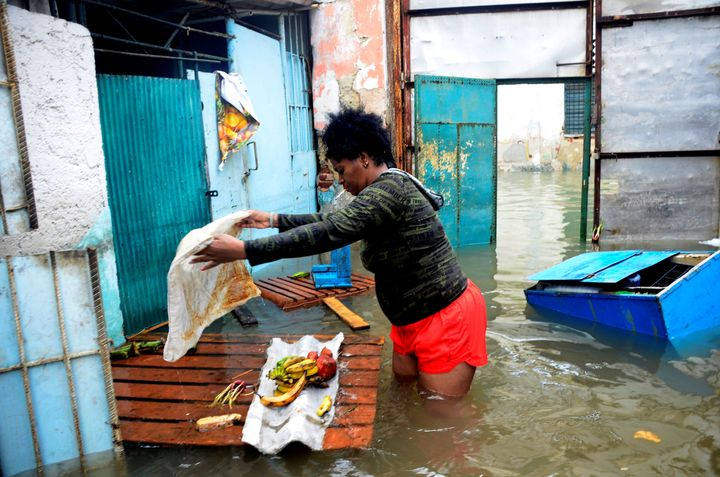 A woman tries to rescue some food from her flooded house in downtown Havana, on September 10, 2017.