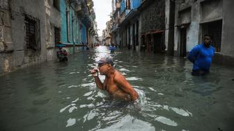 TOPSHOT - A Cuban wades through a flooded street in Havana, on September 10, 2017. Deadly Hurricane Irma battered central Cuba on Saturday, knocking down power lines, uprooting trees and ripping the roofs off homes as it headed towards Florida. Authorities said they had evacuated more than a million people as a precaution, including about 4,000 in the capital.  / AFP PHOTO / YAMIL LAGE        (Photo credit should read YAMIL LAGE/AFP/Getty Images)