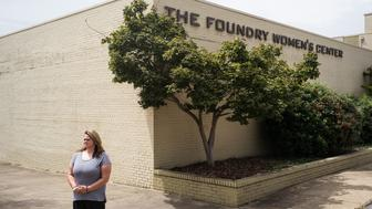 """BESSEMER, AL – AUGUST 29, 2017: Trinity McGuffie, 37, stands outside The Foundry Women's Center. McGuffie is a a graduate of a recovery program led by The Foundry Ministries, a religious nonprofit that provides """"rescue, recovery and re-entry"""" programs in the Christian context for recovering addicts and ex-inmates – a population proven to be at high risk of untreated mental illness. In response to the lack of government provided mental health services, faith-based facilities like The Foundry are bridging the gap by offering their own variety of services to serve the mentally ill."""