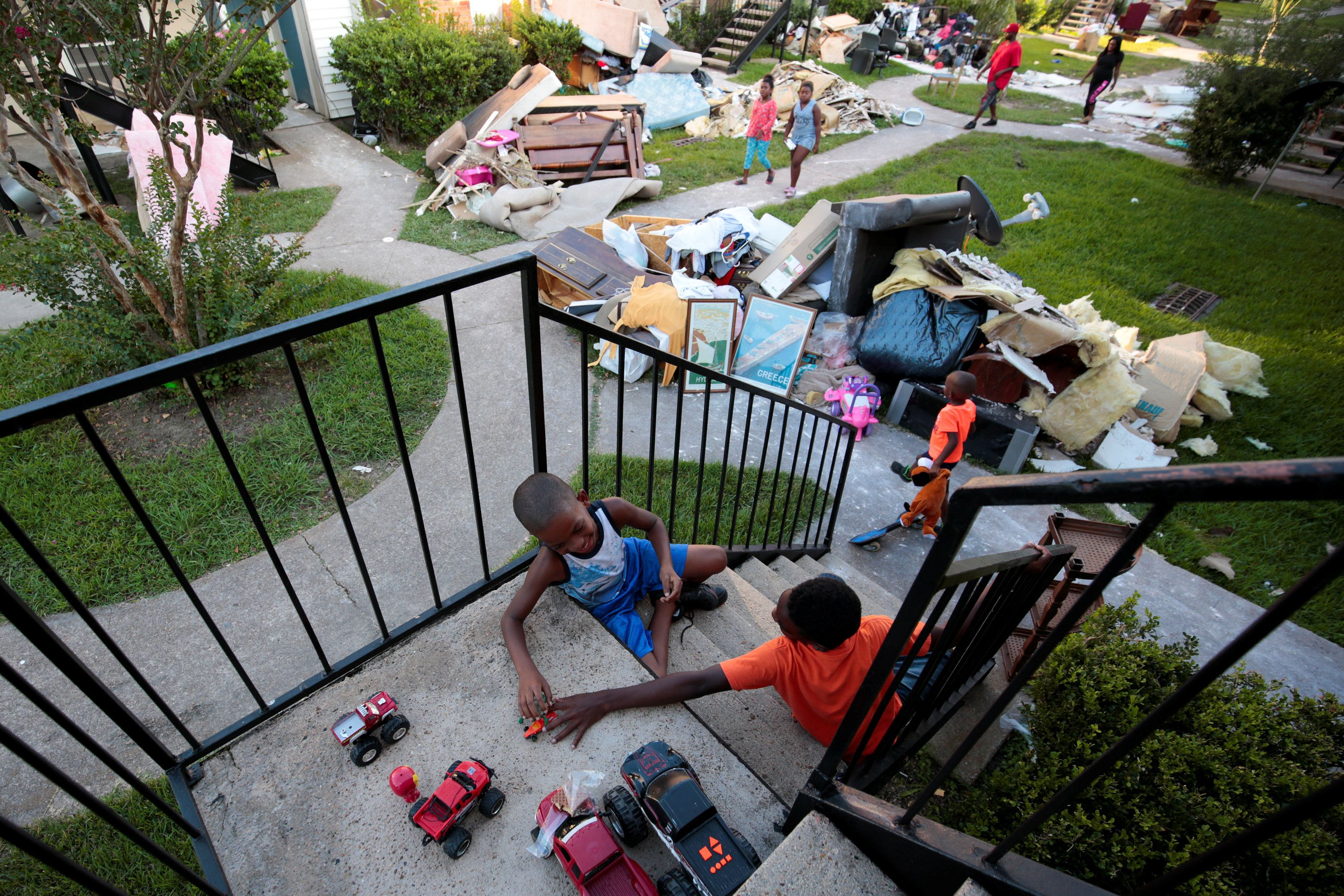 From left, Darius Smith, 9,  Kameron Smith, 4, and Deandre Green, 10, play with toys that they found in the piles of destroyed property at Crofton Place Apartments in the aftermath of Hurricane Harvey in Houston, Texas, U.S. September 8, 2017. The children's apartment was destroyed by the flood waters. Picture taken September 8, 2017. REUTERS/Chris Aluka Berry