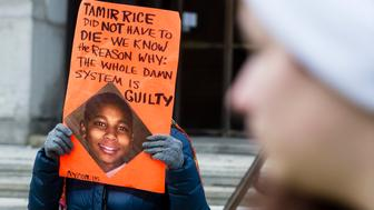 CLEVELAND, OH - NOVEMBER 26: An unidentified woman protests the death of 12-year old Tamir Rice in Cleveland, Ohio, on November 26. Rice was shot by a Cleveland Police Officer responding to a 911 call about a child waving a gun, discovered to be a toy after the shooting, outside the Cudell Recreation Center on Cleveland's near west side. (Photo by Angelo Merendino/Corbis via Getty Images)