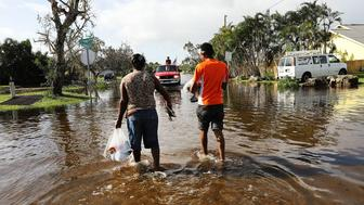 NAPLES, FL - SEPTEMBER 11:  A couple walk through the flooded streets the morning after Hurricane Irma swept through the area on September 11, 2017 in Naples, Florida. Hurricane Irma made another landfall near Naples yesterday after inundating the Florida Keys. Electricity was out in much of the region with localized flooding.  (Photo by Spencer Platt/Getty Images)