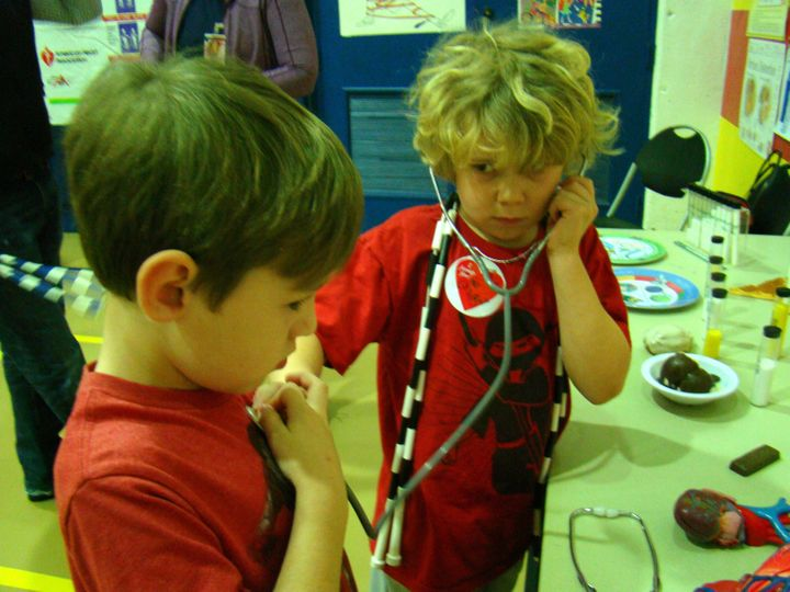 <p>With a jump rope around his and a stethoscope in his ears, one of Kris' students listens to another's heart beat.</p>