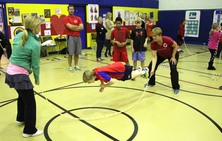 <p>Kris turns one end of the rope as a student performs a trick move.</p>