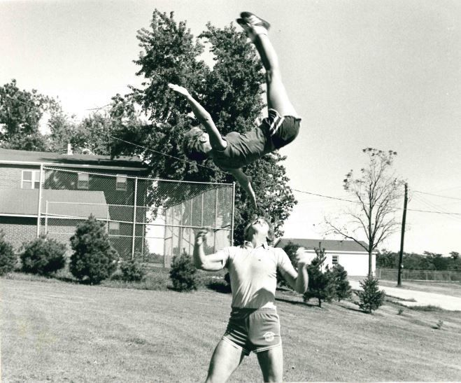 Kris doing a bird flip with Chuck, her fellow cheerleader and circus performer who would become her husband.