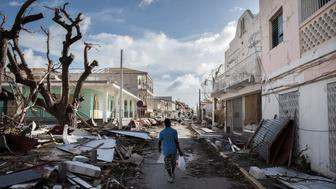 TOPSHOT - A man walks on a street covered in debris after hurricane Irma hurricane passed on the French island of Saint-Martin, near Marigot on September 8, 2017.  Officials on the island of Guadeloupe, where French aid efforts are being coordinated, suspended boat crossings to the hardest-hit territories of St Martin and St Barts where 11 people have died. Two days after Hurricane Irma swept over the eastern Caribbean, killing at least 17 people and devastating thousands of homes, some islands braced for a second battering from Hurricane Jose this weekend. / AFP PHOTO / Martin BUREAU        (Photo credit should read MARTIN BUREAU/AFP/Getty Images)