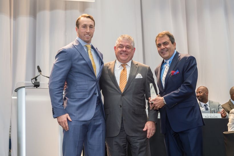 Linebacker Sean Lee (left) is awarded the Defensive MVP Award by Rusty Smith, GM of Neiman Marcus Willow Bend (center) and St