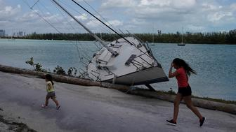 Children run past a boat that has come ashore following Hurricane Irma in Key Biscayne, Florida, U.S., September 11, 2017. REUTERS/Carlo Allegri