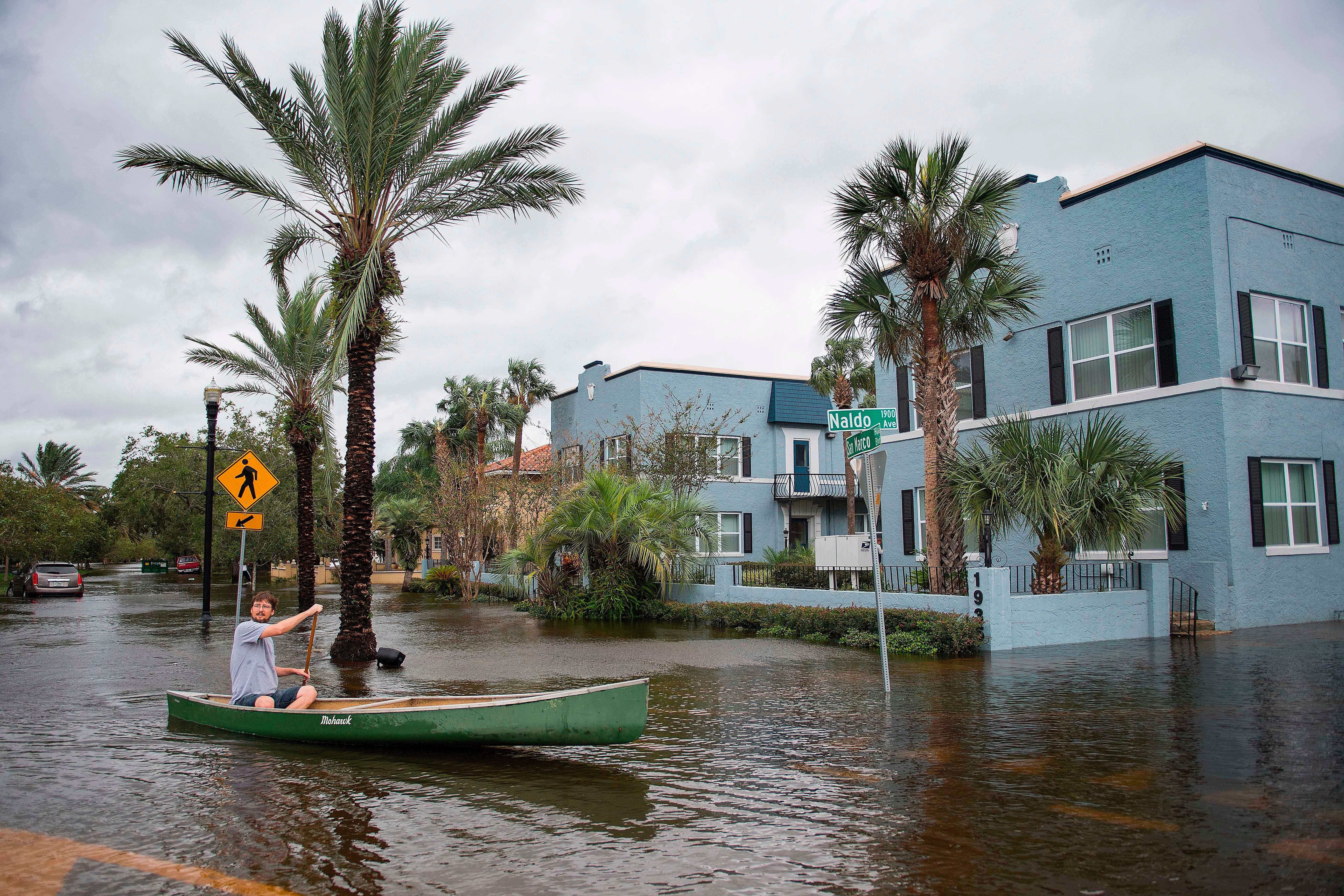A man canoes through the flooded streets of the San Marco historic district of Jacksonville, Florida, on September 11, 2017, after storm surge from Hurricane Irma left the area flooded. / AFP PHOTO / JIM WATSON        (Photo credit should read JIM WATSON/AFP/Getty Images)