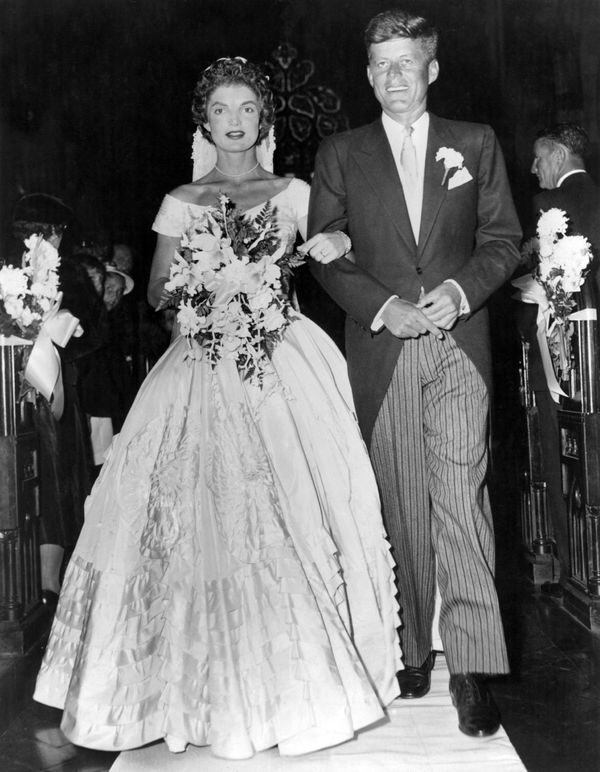 Senator John Fitzgerald Kennedy (1917 - 1963), Democratic senator for Massachusetts, escorts his bride Jacqueline Lee Bouvier