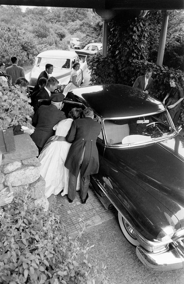 Elevated view as well-wishers gather around the car that carried newly wed future US President John F Kennedy and Jacqueline