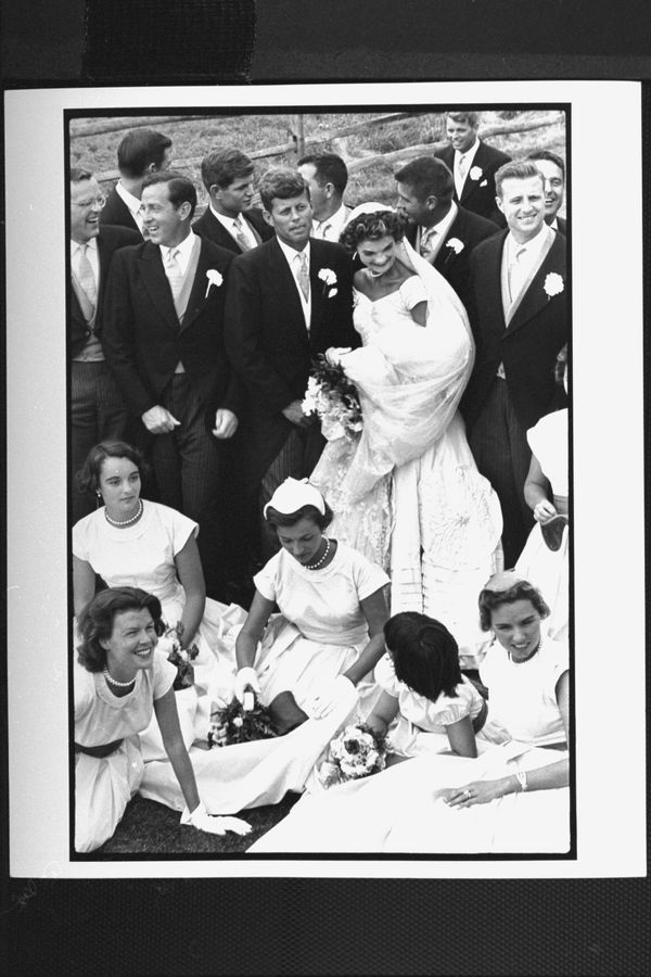 Sen. John Kennedy & his bride Jacqueline in their wedding attire, standing with 10 ushers incl. Teddy & Bobby Kennedy as 4 br