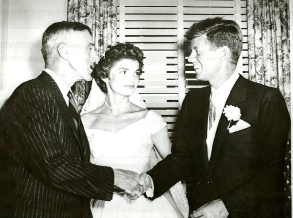 Senator Leverett Saltonstall congratulates Sen. John F. Kennedy at the wedding reception as Kennedy's wife, Jacqueline Bouvie