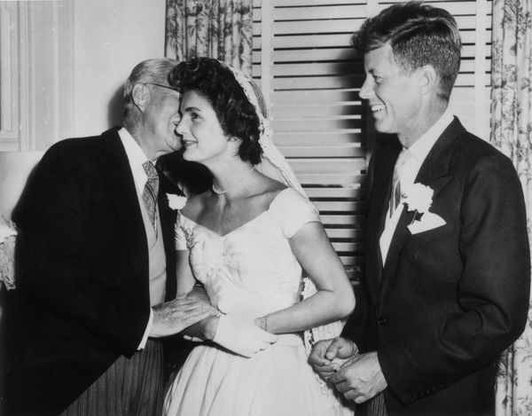 Joseph Kennedy (1888 - 1969) whispers to his new daughter-in-law Jacqueline Bouvier (1929 - 1994) on her wedding day as her h