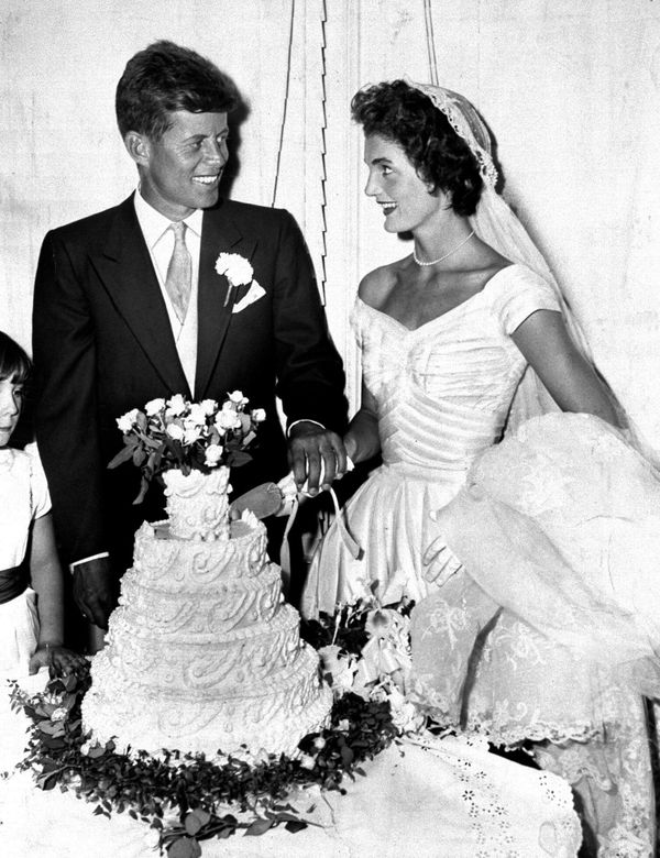 President John F. Kennedy with wife Jacqueline cut the cake at their wedding in Newport, Rhode Island. (Photo by Pat Candido/