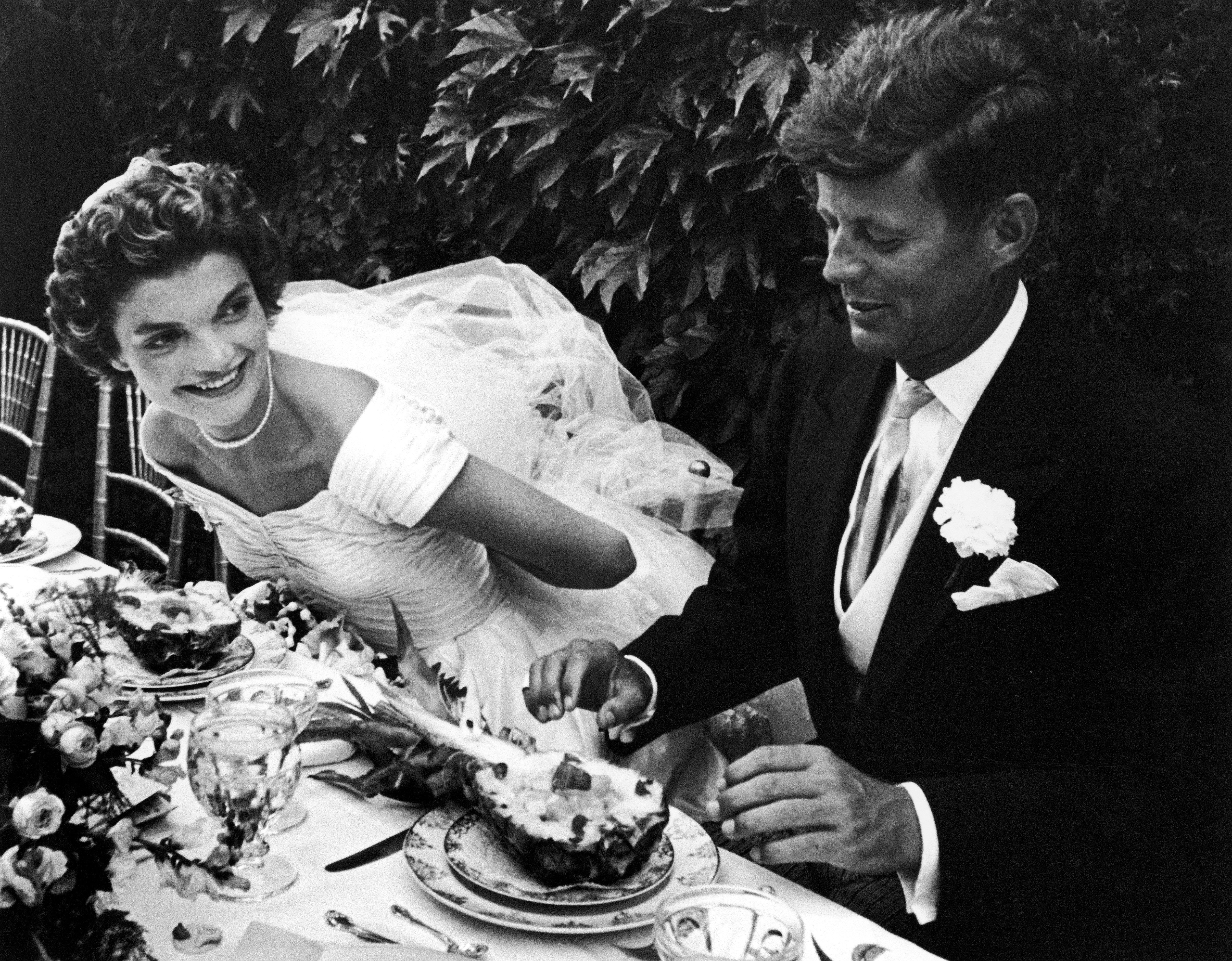Senator John Kennedy and bride Jacqueline sitting together outdoors at table, eating pineapple salad, at their wedding recept