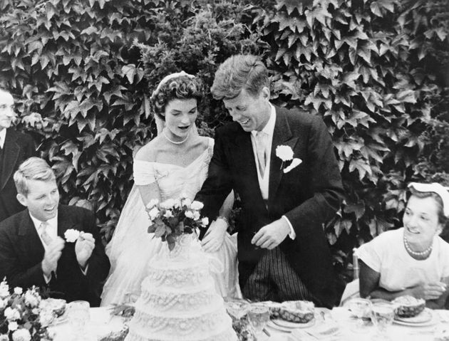 The couple cut their wedding cake at the reception. Kennedy's brother Robert Kennedy (left) looks