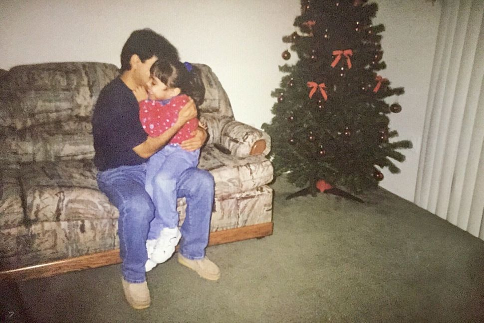 Karla Perez, as a child, with her dadat Christmastime.