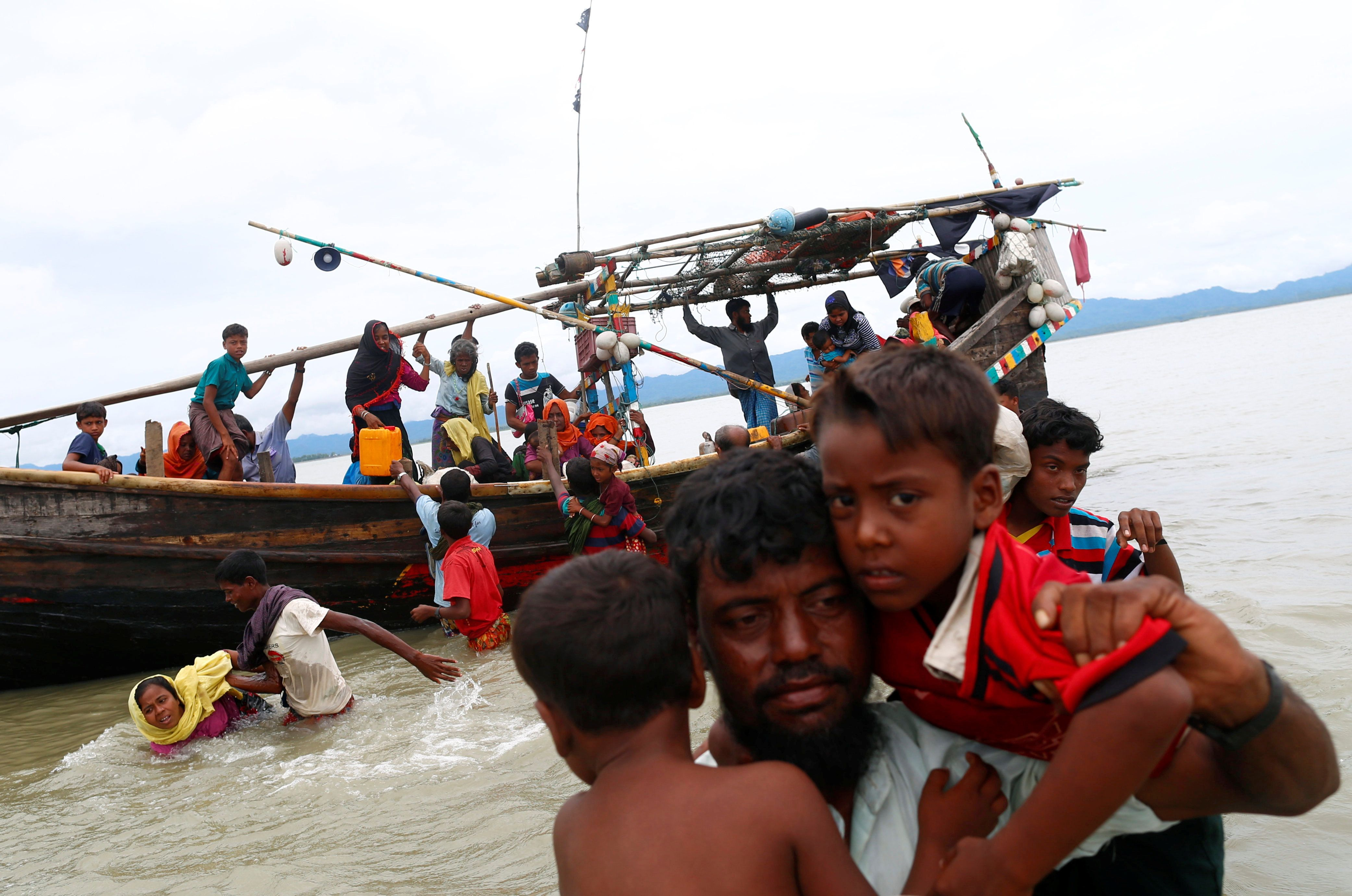 Rohingya refugees walk to the shore after crossing the Bangladesh-Myanmar border by boat through the Bay of Bengal in Shah Porir Dwip, Bangladesh, September 10, 2017. REUTERS/Danish Siddiqui