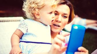 Young beautiful mother takes selfie with her daughter during a walk outdoors. Toned image