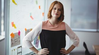 Portrait of confident executive standing with hands on hip in office