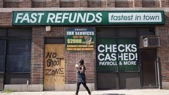 A woman walks past a boarded storefront with a message to end shootings in the Sandtown neighborhood in west Baltimore on August 8, 2017. Baltimore, a city of 2.8 million, is troubled by drug use, poverty and racial segregation problems. In 2016 violent crime in Baltimore was up 22 percent and murders up 78 percent, according to Attorney General Jeff Sessions. / AFP PHOTO / MANDEL NGAN        (Photo credit should read MANDEL NGAN/AFP/Getty Images)