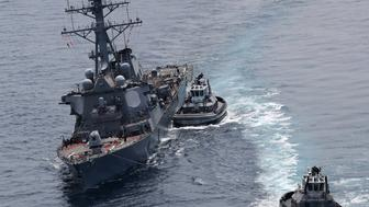 This picture shows the guided missile destroyer USS Fitzgerald next to tugboats off the Shimoda coast after it collided with a Philippine-flagged container ship on June 17, 2017. The US Navy destroyer collided with ACX Crystal cargo ship off the coast of Japan, leaving seven crew members from the American vessel unaccounted for, the Japanese Coast Guard said. / AFP PHOTO / JIJI PRESS / STR / Japan OUT        (Photo credit should read STR/AFP/Getty Images)